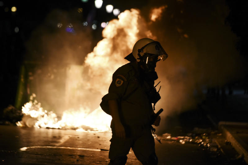CORRECTING TO REMOVE REFERENCE TO ALLEGIANCE OF GROUP CLASHING WITH POLICE - A police officer walks in front of burning garbage cans during clashes with protesters in the northern Greek city of Thessaloniki, Saturday, Sept. 8, 2018. Police in northern Greece have clashed with protesters outside an international trade fair where prime minister Tsipras made a keynote speech. (AP Photo/Giannis Papanikos)