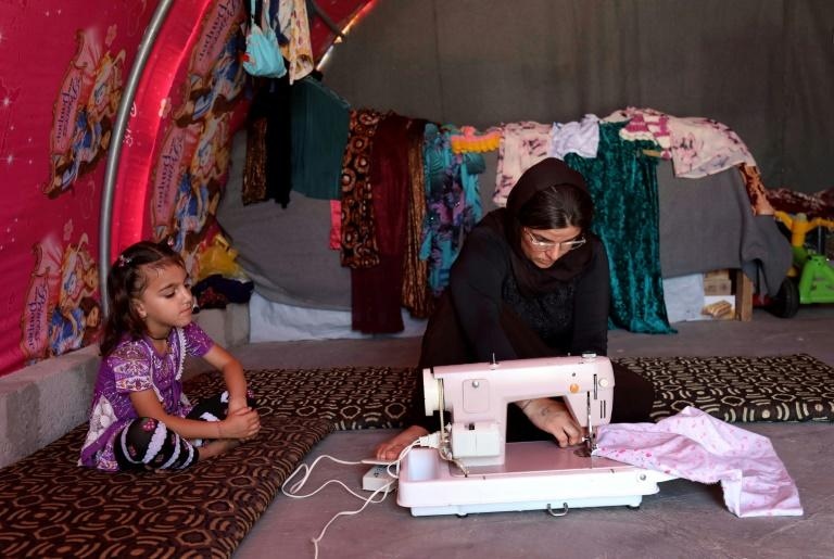Yazidi survivor Layleh Shemmo sews inside her tent in the Khonke displacement camp in northwestern Iraq on June 24, 2019
