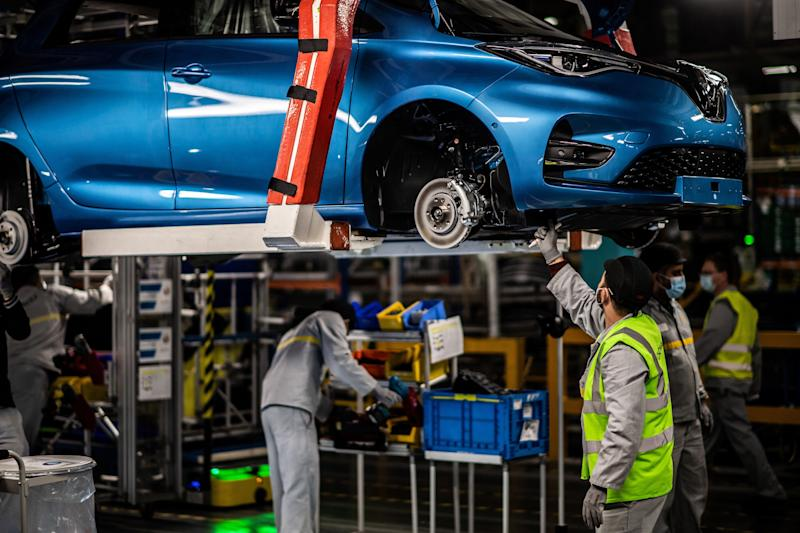 Employees wearing protective masks against the spread of the novel coronavirus, COVID-19, work along the assembly line that produces both the electric vehicle Renault Zoe and the hybrid vehicle Nissan Micra, at Flins-sur-Seine, the largest Renault production site in France on May 6, 2020. - To reopen following the March 17th lockdown across France, the factory has had to enforce all the safety measure required to reduce any spread of COVID-19 at the assembly plant, with workers having to wear protective masks and gloves and diving the assembly line into individual parts to spot any person-to-person contamination. (Photo by Martin BUREAU / AFP) (Photo by MARTIN BUREAU/AFP via Getty Images)
