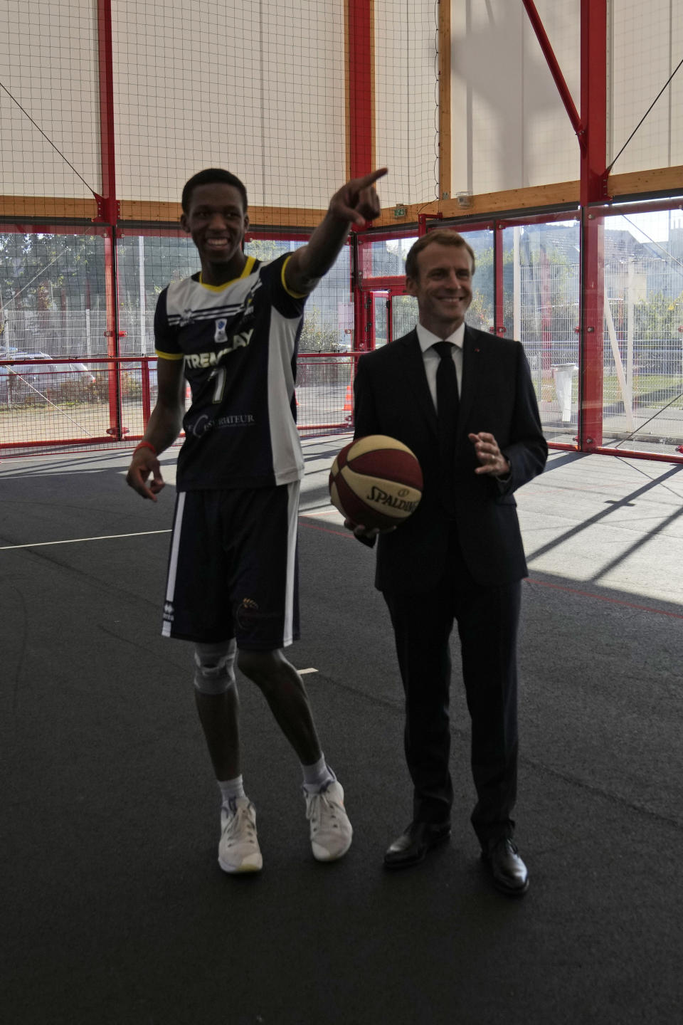 French President Emmanuel Macron holds the ball as he speaks to a member of a basketball team at a basketball playground in Tremblay-en-France, outside Paris, Thursday, Oct.14, 2021. French President Emmanuel Macron will promote sports ahead of the 2024 Olympic Games in Paris. (AP Photo/Francois Mori, Pool)