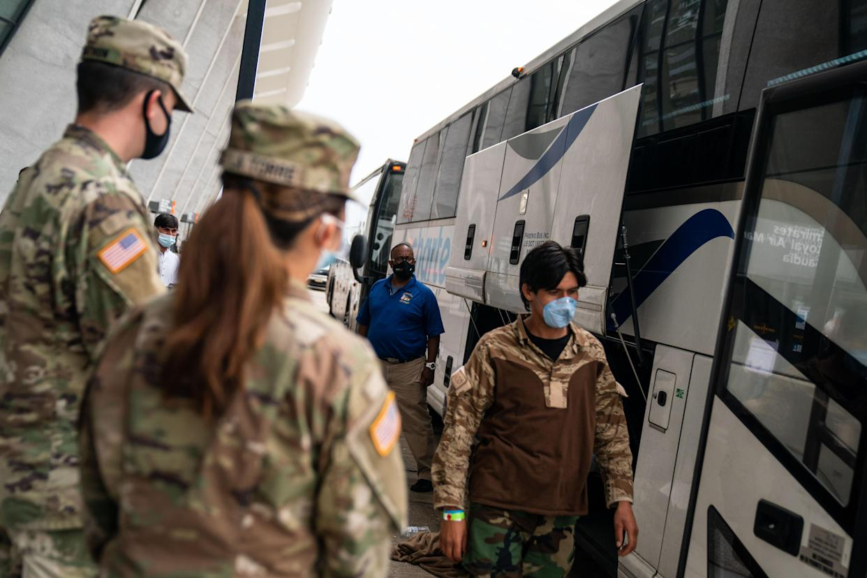 DULLES, VA - AUGUST 31: Evacuees who fled Afghanistan walk through the terminal to board buses that will take them to a processing center, at Dulles International Airport on Tuesday, Aug. 31, 2021. Refugees continue to arrive in the United States, after the US withdrew troops from Afghanistan. (Kent Nishimura / Los Angeles Times via Getty Images)