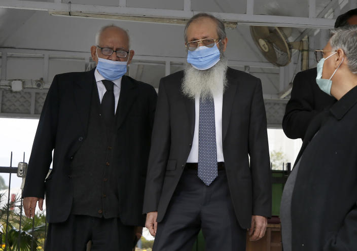 Ahmed Saeed Sheikh, center, father of British-born Pakistani Ahmed Omar Saeed Sheikh, leaves with his lawyer Rauf A. Sheikh, following a hearing of the Daniel Pearl case in the Supreme Court, in Islamabad, Pakistan, Tuesday, Feb. 2, 2021. Pakistan's Supreme Court on Tuesday ordered the Pakistani-British man acquitted of the 2002 gruesome beheading of American journalist Daniel Pearl off 'death row' and moved to a so-called government 'safe-house'. (AP Photo/Anjum Naveed)