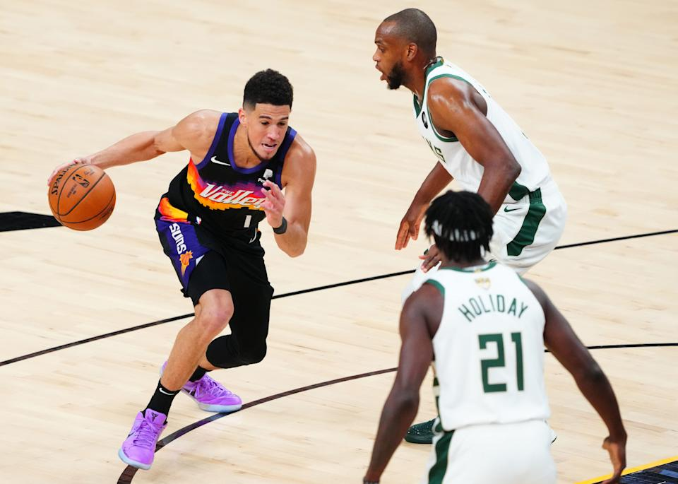 Suns star Devin Booker (left) is in for one awkward plane ride to Tokyo with the Bucks' Khris Middleton and Jrue Holiday, who just beat him in the NBA Finals. (Mark J. Rebilas-USA TODAY Sports)