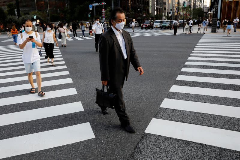 FILE PHOTO: People wearing protective masks make their way at a business district in Tokyo