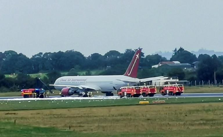Firecrews attend an Omni Air International aircraft on the tarmac at Shannon Airport in County Clare, western Ireland, after  a fire broke out on the undercarriage of the plane on the runway