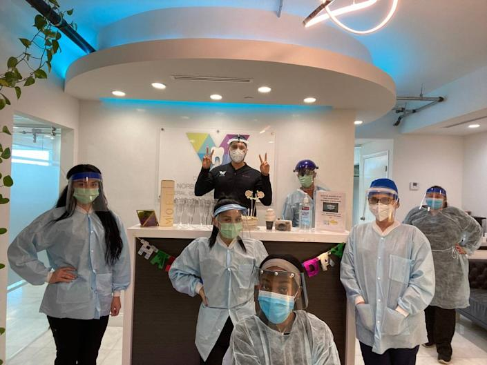 Dr. Norberto Camacho, center, a 35-year-old dentist at Dental World Miami in Brickell poses in full protective equipment with his staff, from left, Zaria Figueredo, Gabriela Rivas, Jose D. Contreras, Blanca R. Camacho, Aracely Gonzalez, Mesha Gilmore and Sandra Caceres.