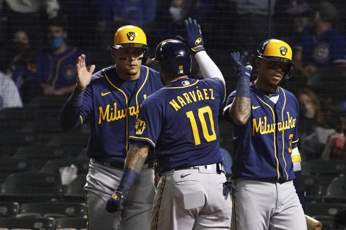 Milwaukee Brewers' Omar Narvaez (10) is greeted after hitting a three-run home run against the Chicago Cubs during the seventh inning of a baseball game, Monday, April 5, 2021, in Chicago. (AP Photo/David Banks)
