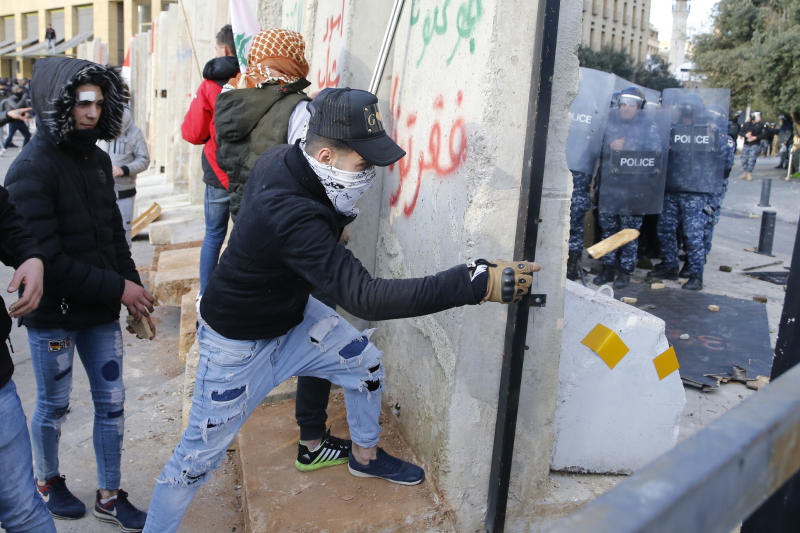 Demonstrators throw stones toward riot police during a protest against a parliament session preparing a vote of confidence for the new government in downtown Beirut, Lebanon, Tuesday, Feb. 11, 2020. (AP Photo/Bilal Hussein)