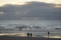Members of the public walk on the beach at Blackpool, England, Wednesday Nov. 4, 2020. Britain is preparing to join large swathes of Europe in a coronavirus lockdown designed to save its health care system from being overwhelmed. Pubs, along with restaurants, hairdressers and shops selling non-essential items will have to close Thursday until at least Dec. 2. (AP Photo/Jon Super)