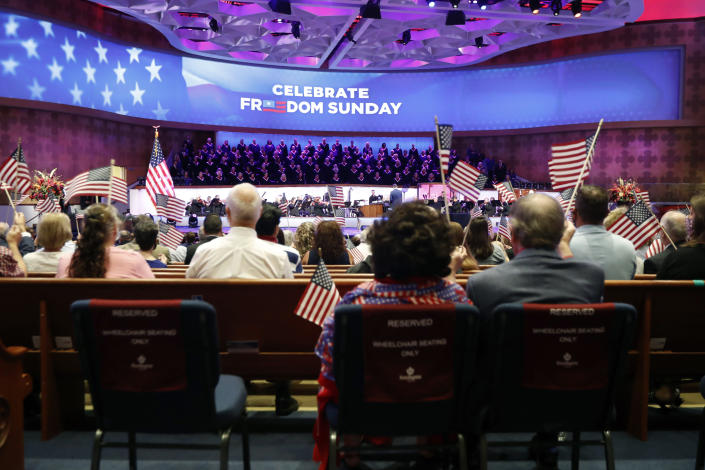 Participants wave flags before Pence delivers his remarks at the First Baptist Church of Dallas. (Tony Gutierrez / AP)