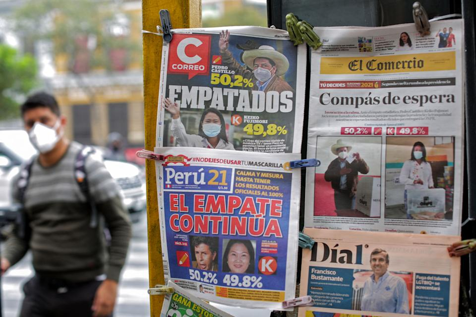 A man walks near Peruvian newspapers front pages displayed at a kiosk in Lima on June 7, 2021, the day after the presidential runoff election. - Right-wing populist Keiko Fujimori held a narrow lead Monday in Peru's presidential election, but the crisis-hit nation's race was too close to call as votes were still being tabulated from countryside bastions of support for radical leftist Pedro Castillo. With over 95% of the votes tallied, the result of the runoff election is still unknown. (Photo by Luka GONZALES / AFP) (Photo by LUKA GONZALES/AFP via Getty Images)