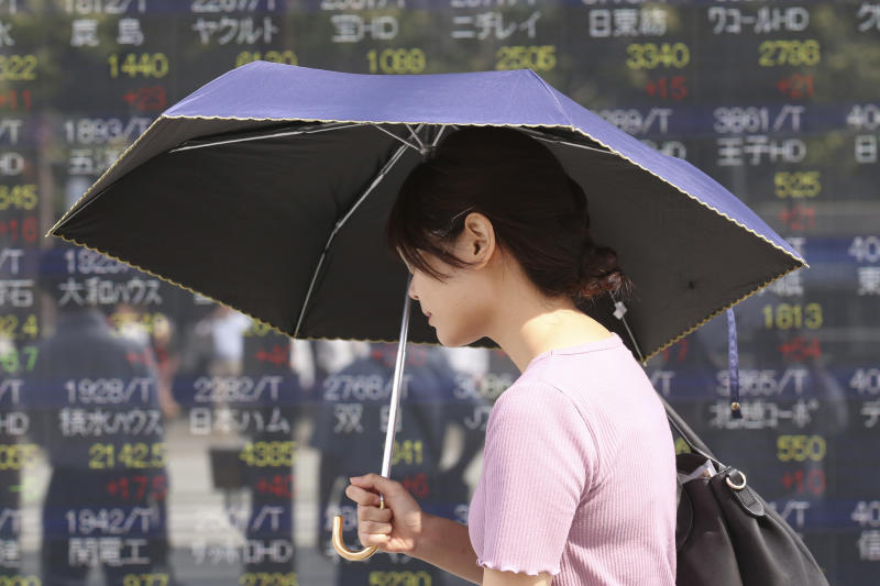 A woman walks by an electronic stock board of a securities firm in Tokyo, Tuesday, Oct. 1, 2019. Shares rose in Asia on Tuesday, with markets in Hong Kong and Shanghai closed for a national day holiday. (AP Photo/Koji Sasahara)