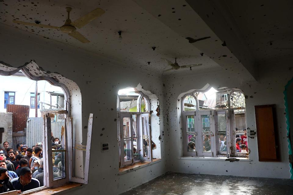 People inspect a mosque partially damaged during a gunbattle between Indian soldiers and suspected militants in Shopian.