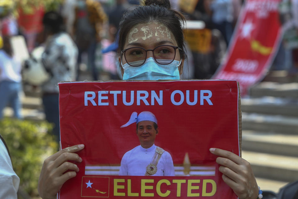"""An anti-coup protester with thanaka, a traditional face paste with letters CDM, representing """"Civil Disobedience Movement,"""" displays a placard with an image of deposed Myanmar President Win Myint during a street march in Mandalay, Myanmar, Thursday, Feb. 25, 2021. Social media giant Facebook announced Thursday it was banning all accounts linked to Myanmar's military as well as ads from military-controlled companies in the wake of the army's seizure of power on Feb. 1. (AP Photo)"""