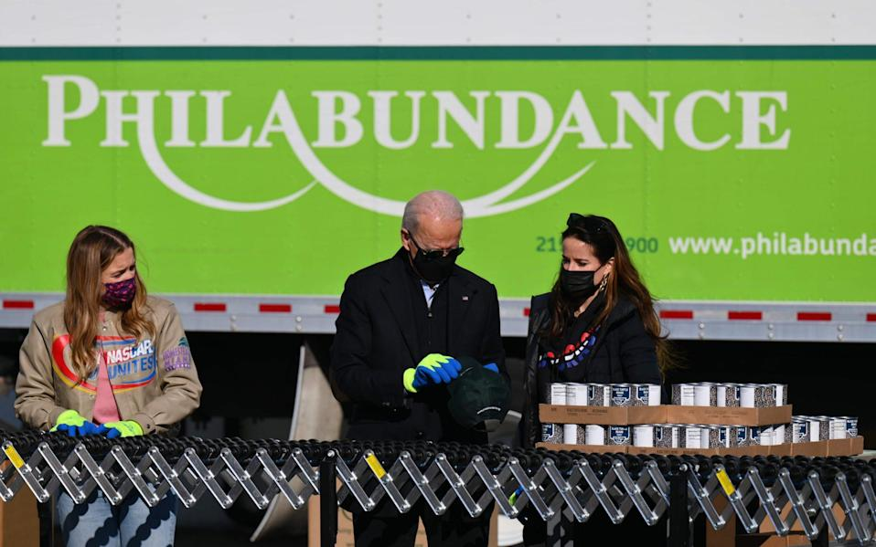 Joe Biden(C),stands with his grandaughter Finnegan(L) and daughter Ashley(R) as they pack up food donations at Philabundance, Philadelphia's largest hunger relief organisation - AFP