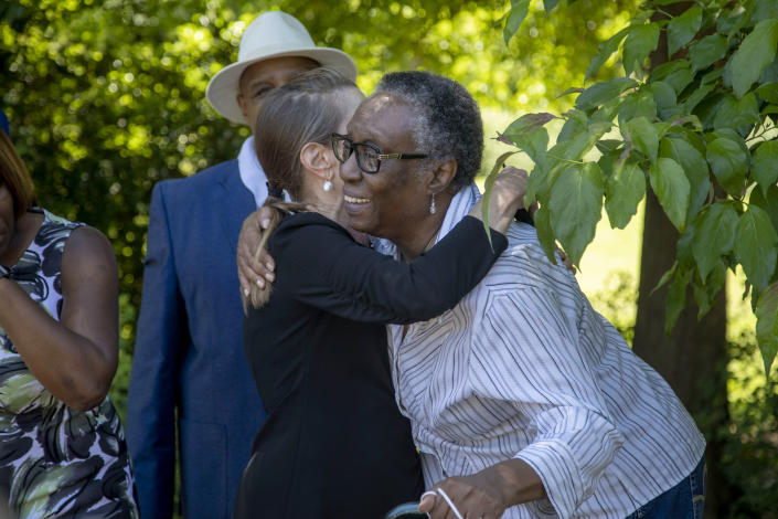D. E. Smith, right, chair of the DeKalb Remembrance Project, which operates within the DeKalb County NAACP, receives a hug from Druid Hill resident Schaune Griffin, following a short ceremony to erect a historical marker for Porter Flournoy Turner, who was lynched in 1945, in Atlanta's Druid Hills community, Thursday, May 6, 2021. Both women participated in getting the marker installed. (Alyssa Pointer/Atlanta Journal-Constitution via AP)