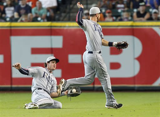 Tampa Bay Rays second baseman Ben Zobrist, right, leaps out of the way of right fielder Wil Myers, who catches the ball for an out on Houston Astros' Jose Altuve during the first inning of a baseball game Thursday, July 4, 2013, in Houston. (AP Photo/Patric Schneider)