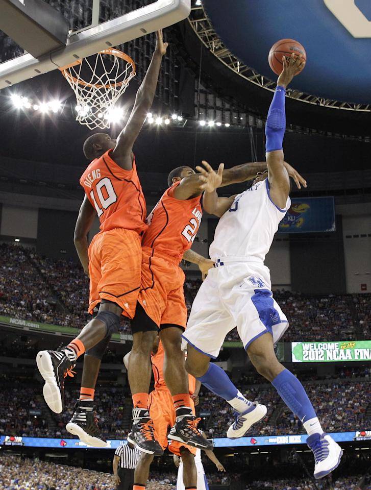 Kentucky's Terrence Jones, right, shoots over Louisville's Chane Behanan, center, and Gorgui Dieng, left, during the first half of an NCAA Final Four semifinal college basketball tournament game Saturday, March 31, 2012, in New Orleans. (AP Photo/Mark Humphrey)