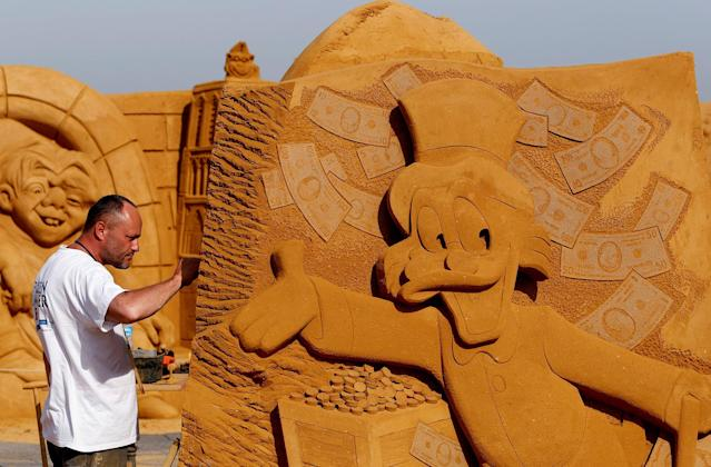 "<p>Sand carver Teimur Ilya Shanin from Russia works on a sculpture during the Sand Sculpture Festival ""Disney Sand Magic"" in Ostend, Belgium June 22, 2017. (Yves Herman/Reuters) </p>"