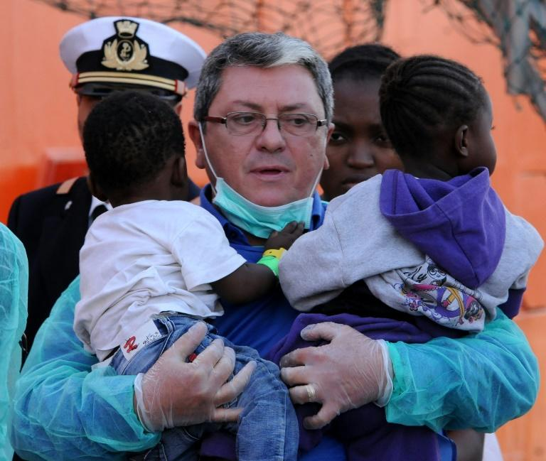 A rescuer holds two young children as migrants disembark from the Siem Pilot ship on October 24, 2016 in Palermo after rescue operations off the coast of Libya three days earlier