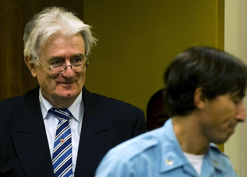 Suspected war criminal and the former leader of Serbs in Bosnia, Radovan Karadzic, left, enters the court room to start his defense at the U.N. war crimes tribunal in the Hague in The Hague, Netherlands, Tuesday Oct. 16, 2012. (AP Photo/Robin van Lonkhuijsen, Pool)