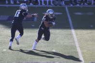Nevada quarterback Carson Strong hands off to running back Toa Taua in the first half of an NCAA football game against San Diego State, Saturday, Nov. 21, 2020, Reno, Nev. (AP Photo/Lance Iversen)