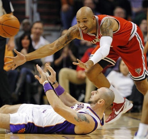 Phoenix Suns' Marcin Gortat, bottom, makes a pass from the floor as Milwaukee Bucks' Drew Gooden closes in during the first half of an NBA basketball game, Sunday, Jan. 8, 2012, in Phoenix. (AP Photo/The Arizona Republic, David Kadlubowski) MARICOPA COUNTY OUT; MAGS OUT; NO SALES