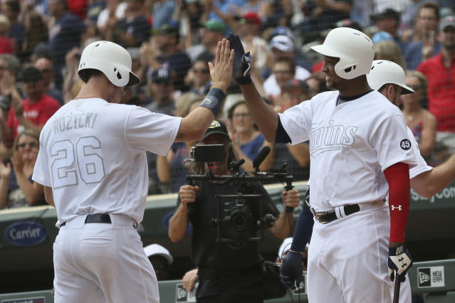 Minnesota Twins' Max Kepler high-fives teammate Jonathan Schoop after scoring on a home run by C.J. Cron against the Detroit Tigers during the fourth inning of a baseball game Sunday, Aug. 25, 2019, in Minneapolis. (AP Photo/Stacy Bengs)