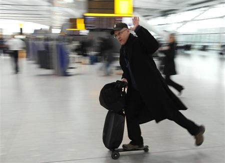 A passenger travels on a scooter with his luggage at Heathrow airport in London