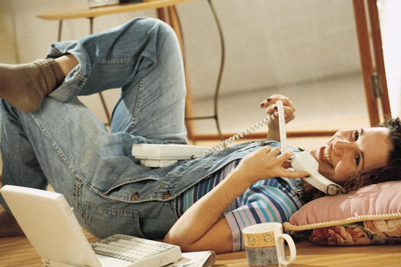 Woman laying on floor and talking on telephone
