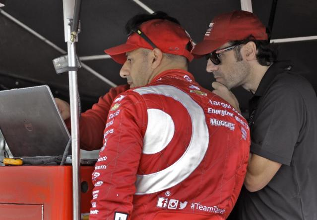 Driver Tony Kanaan, left, of Brazil and his driver coach Dario Franchitti, of Scotland, look over statistics after a practice run for the IndyCar Firestone Grand Prix of St. Petersburg auto race Friday, March 28, 2014, in St. Petersburg, Fla. The race takes place Sunday afternoon. (AP Photo/Chris O'Meara)