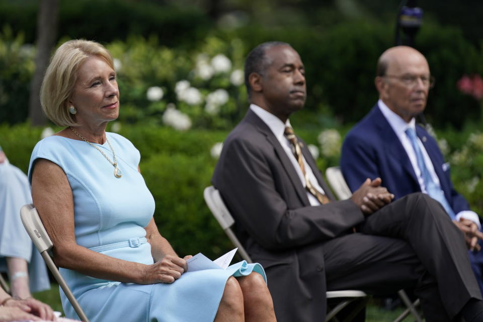 """From left, Education Secretary Betsy DeVos, Housing and Urban Development Secretary Ben Carson and Commerce Secretary Wilbur Ross listen as President Donald Trump speaks before signing an executive order on the """"White House Hispanic Prosperity Initiative,"""" in the Rose Garden of the White House, Thursday, July 9, 2020, in Washington. (AP Photo/Evan Vucci)"""
