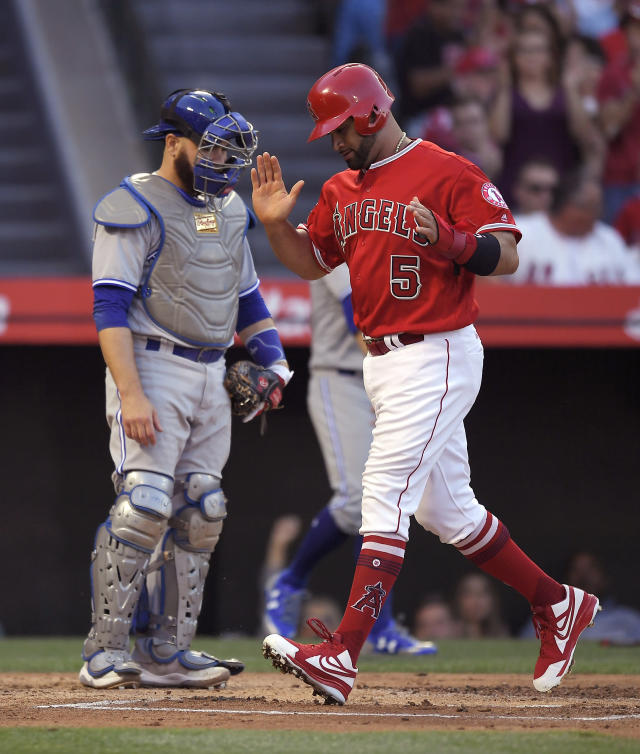 Los Angeles Angels' Albert Pujols, right, claps as he scores on a single by Luis Valbuena as Toronto Blue Jays catcher Russell Martin stands at the plate during the first inning of a baseball game Friday, June 22, 2018, in Anaheim, Calif. (AP Photo/Mark J. Terrill)