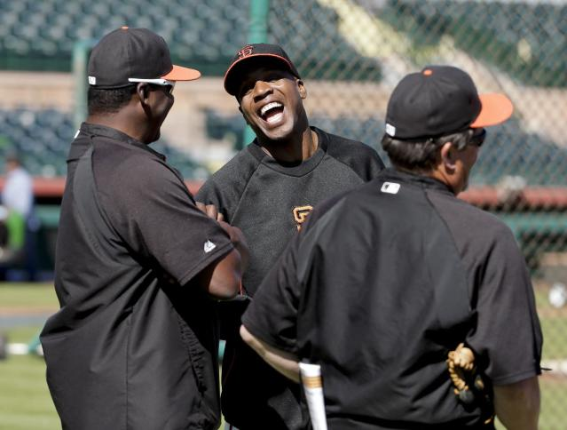 San Francisco Giants former player Barry Bonds, middle, talks with other coaches during batting practice before a spring training baseball game between the Giants and the Chicago Cubs in Scottsdale, Ariz., Monday, March 10, 2014. Bonds starts a seven day coaching stint today. (AP Photo/Chris Carlson)
