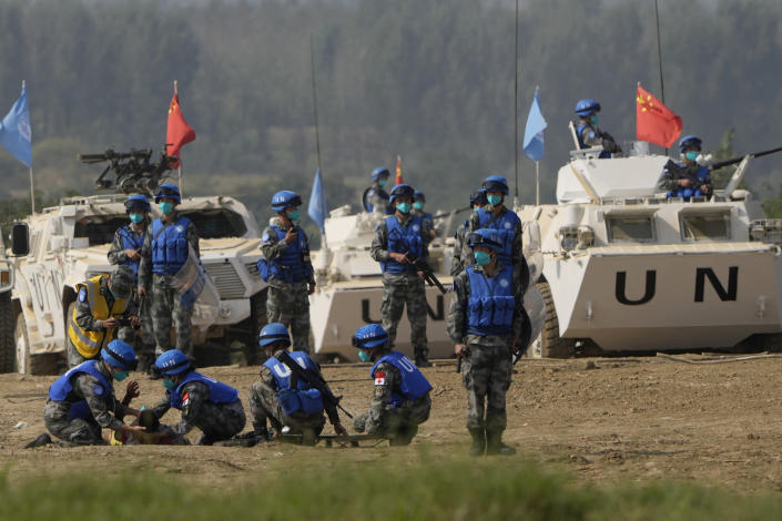 United Nations troop tend to a participant playing the role of injured civilian during a scenario where they pacify local civilians fighting over water resource during the Shared Destiny 2021 drill at the Queshan Peacekeeping Operation training base in Queshan County in central China's Henan province Wednesday, Sept. 15, 2021. Peacekeeping troops from China, Thailand, Mongolia and Pakistan took part in the 10 days long exercise that field reconnaissance, armed escort, response to terrorist attacks, medical evacuation and epidemic control. (AP Photo/Ng Han Guan)