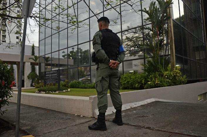 A policeman stands guard outside the Mossack-Fonseca law firm offices in Panama City during a raid on April 12, 2016 (AFP Photo/Ed Grimaldo)