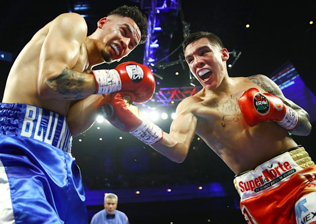 """Oscar Valdez (R) punches <a class=""""link rapid-noclick-resp"""" href=""""/ncaaf/players/290745/"""" data-ylk=""""slk:Adam Lopez"""">Adam Lopez</a> during their super featherweight title eliminator fight Saturday at the Cosmopolitan in Las Vegas. (Mikey Williams/Top Rank)"""
