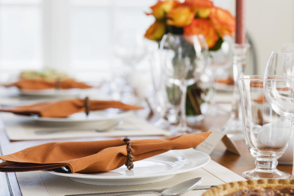 fine china with orange napkins on Thanksgiving dinner table