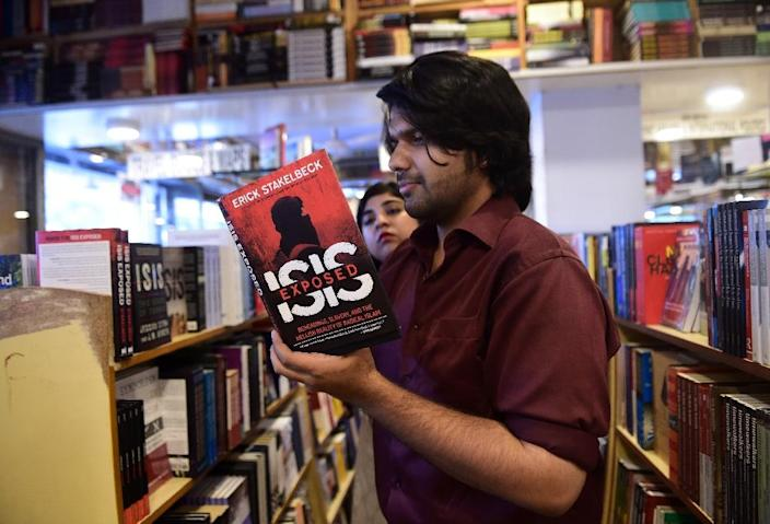 Kunwar Khuldune Shahid (front), one of the Pakistani founders of the Khabaristan Times website, poses at a bookstore as co-founder Luavut Zahid (behind), looks on in Islamabad (AFP Photo/Farooq Naeem)
