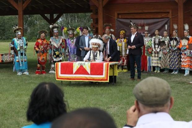 Community members, dancers, Elders, Premier Scott Moe and Prime Minister Justin Trudeau watch as Chief Cadmus Delorme signs the agreement for federal funding to locally control their child welfare services.  (Matt Howard/CBC - image credit)