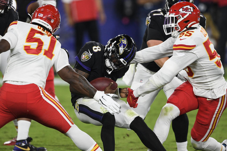 Baltimore Ravens quarterback Lamar Jackson (8) is hit by Kansas City Chiefs defensive ends Michael Danna (51) and Frank Clark (55) during the first half of an NFL football game Monday, Sept. 28, 2020, in Baltimore. (AP Photo/Nick Wass)