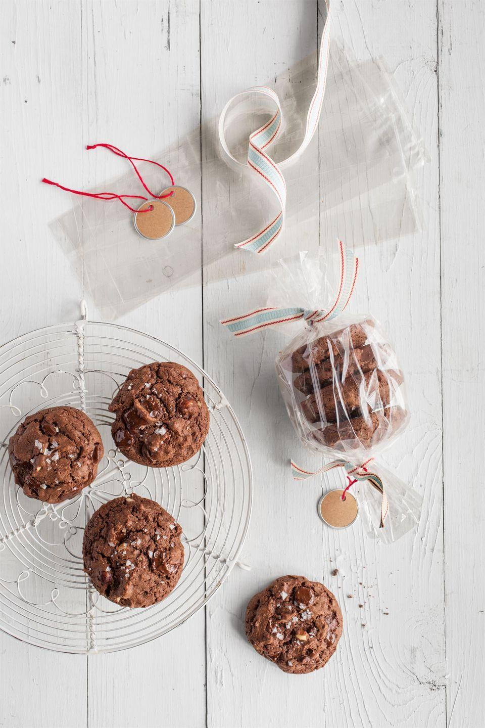 """<p>Stack four cookies in a clear plastic bag, then tie decorative ribbon at each end of the bag to cinch. Trim ends and add a metal-rim tag, and you've got yourself a festive hostess gift.</p><p><strong><a href=""""https://www.countryliving.com/food-drinks/recipes/a36896/triple-chocolate-hazelnut-cookies/"""" rel=""""nofollow noopener"""" target=""""_blank"""" data-ylk=""""slk:Get the recipe"""" class=""""link rapid-noclick-resp"""">Get the recipe</a>.</strong></p><p><a class=""""link rapid-noclick-resp"""" href=""""https://www.amazon.com/dp/B082WF6MG2/?tag=syn-yahoo-20&ascsubtag=%5Bartid%7C10050.g.647%5Bsrc%7Cyahoo-us"""" rel=""""nofollow noopener"""" target=""""_blank"""" data-ylk=""""slk:SHOP ROLLING PINS"""">SHOP ROLLING PINS</a></p>"""