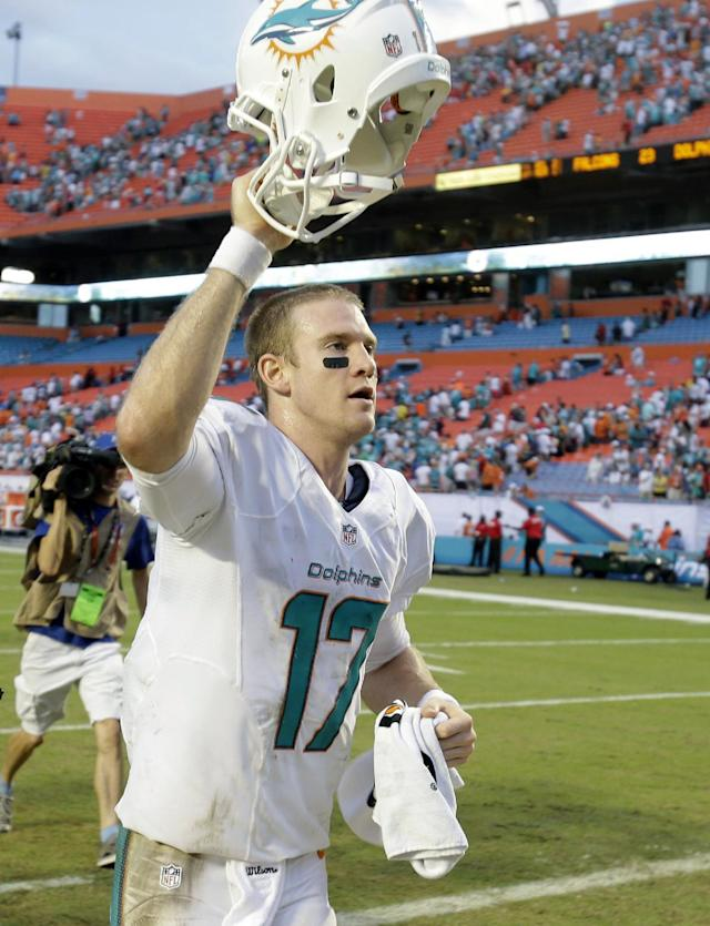 Miami Dolphins quarterback Ryan Tannehill holds up his helmet to fans as he runs off the field after the Dolphins defeated the Atlanta Falcons 27-23 in an NFL football game, Sunday, Sept. 22, 2013, in Miami Gardens, Fla. (AP Photo/Wilfredo Lee)