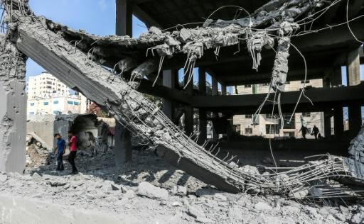 Palestinian youths walk through the wreckage of a building in Gaza City on July 15, 2018, the day after it was hit by Israeli air strikes