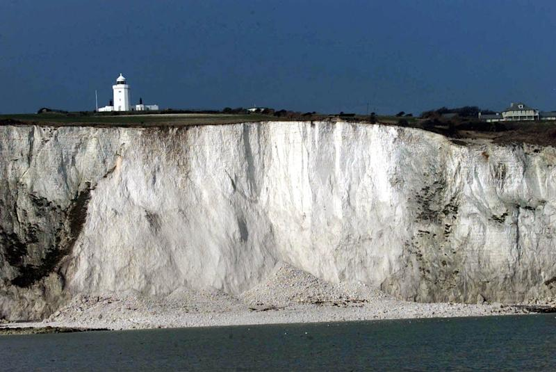 """FILE - This is a Thursday, Feb. 1, 2001. file photo shows the lighthouse on top of the White Cliffs of Dover, England, after a  large segment of chalk fell from the cliff  after a landslide. Philosopher Julian Baggini has a high-altitude new assignment  pondering the significance and symbolism of the White Cliffs of Dover. The National Trust, guardian of the landmarks on England's south cast, has appointed Baggini the cliffs' first writer in residence. Starting Monday, Aug. 20, 2012 he will spend a week living in a cliff-top lighthouse. Baggini said he hoped to learn """"what the white cliffs of Dover mean for British people, including those for whom the cliffs were the first sight of the country which would become their adopted home."""" (AP Photo/Dave Caulkin, File)"""
