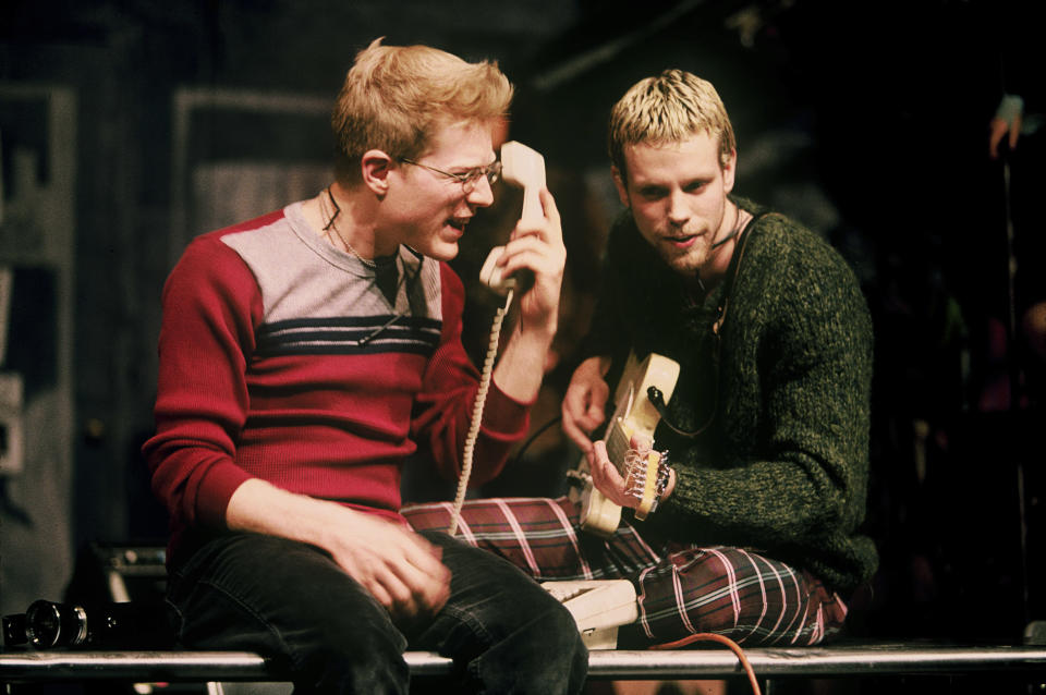 """Anthony Rapp, left, and Adam Pascal appear during a performance of the 1996 musical """"Rent"""" in New York. The New York Theater Workshop will celebrate the 25th anniversary of """"Rent"""" with a gala on March 2 that will be available to stream through March 6. Original cast members will be joined by theater stars such as Lin-Manuel Miranda, Neil Patrick Harris and Ben Platt. (Joan Marcus/Matt Ross Public Relations via AP)"""