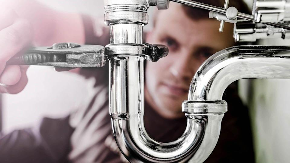 Plumber using a wrench to tighten a siphon under a sink.