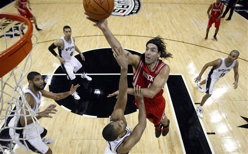 Houston Rockets' Luis Scola (4), of Argentina, sails over San Antonio Spurs' Gary Neal, center, as Spurs' Tim Duncan, left, Danny Green (4) and Tony Parker (9), of France, watch during the second quarter of an NBA basketball game Wednesday, Jan. 11, 2012, in San Antonio. (AP Photo/Eric Gay)
