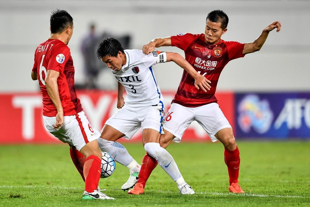 Shoji Gen (centre) of Japan's Kashima Antlers fights for the ball with Huang Bowen of China's Guangzhou Evergrande during their AFC Champions League match in Guangzhou, in China's Guangdong province on May 23, 2017 (AFP Photo/STR)