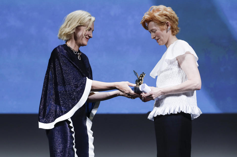 Actress Tilda Swinton, right, holds the Golden Lion for Lifetime Achievement presented by Jury President Cate Blanchett during the opening ceremony of the 77th edition of the Venice Film Festival in Venice, Italy, Wednesday, Sept. 2, 2020. (AP Photo/Domenico Stinellis)
